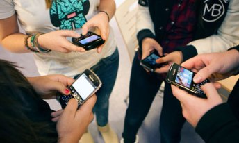 Teenagers using Blackberry mobile phones